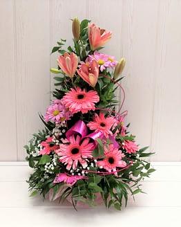 Centro de flores en tonos rosas de frente