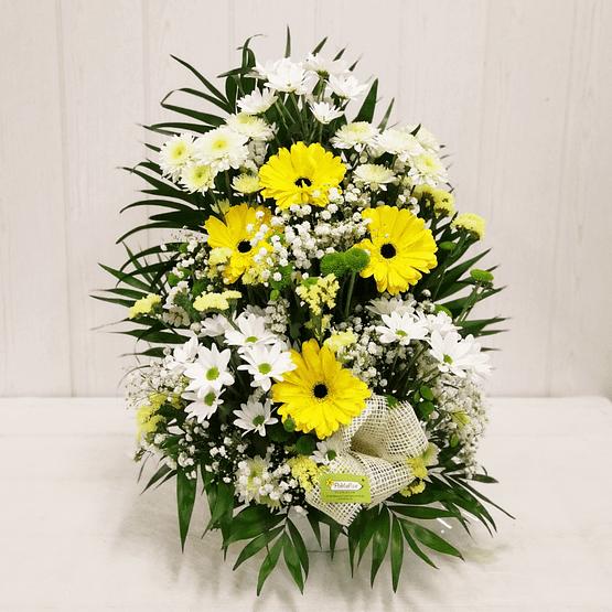 centro de flores en tonos amarillos y blancos de frente