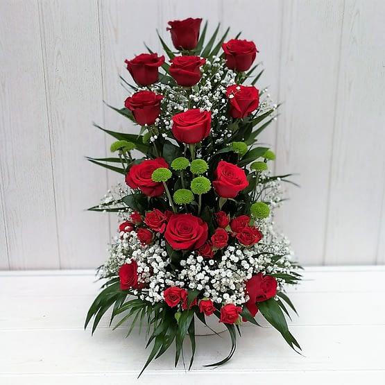 centro de rosas rojas y botón verde de frente