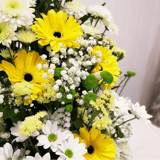 centro de flores en tonos amarillos y blancos de cerca