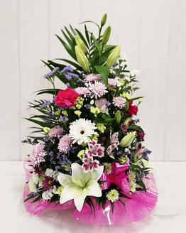 centro de flores en tonos rosas y blancos de frente