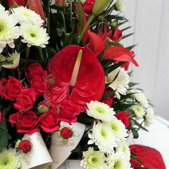 centro de anthurium rojo, margarita blanca y rosa pitiminí de cerca