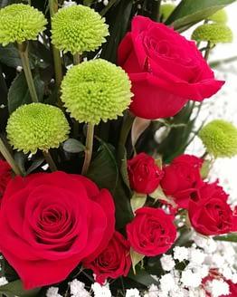 centro de rosas rojas y botón verde de cerca